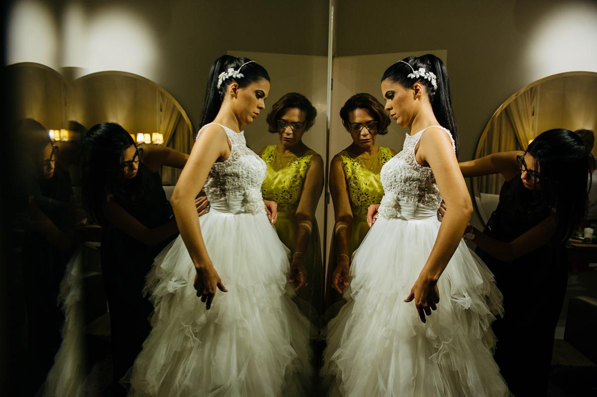 a cerimonialista Carla Rossine e a mãe da noiva ajudam a vestir