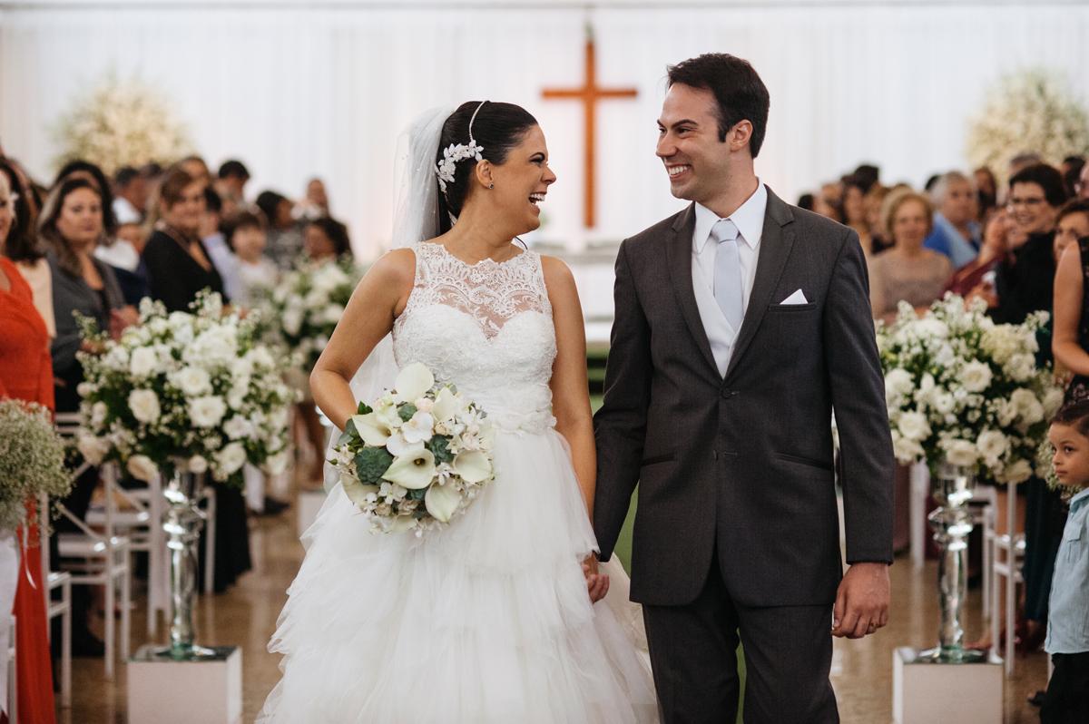 Felizes os noivos deixam a cerimonia