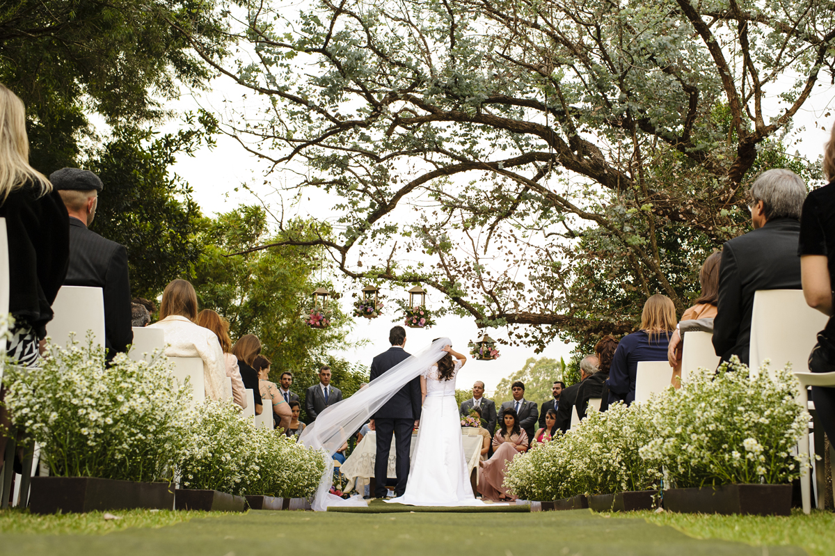 Noiva segura o véu em cerimonia ao ar livre