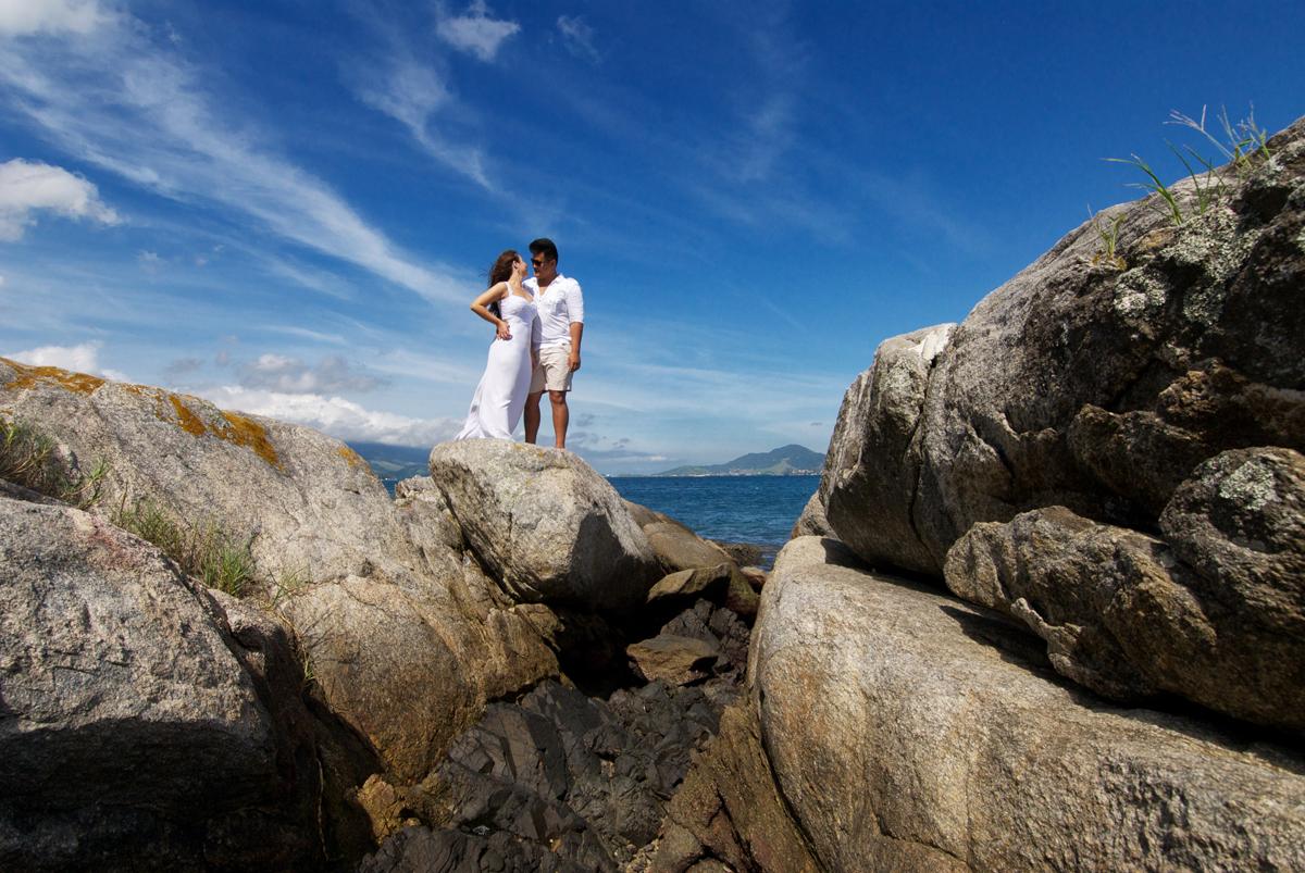 noivos se beijando sobre a rocha