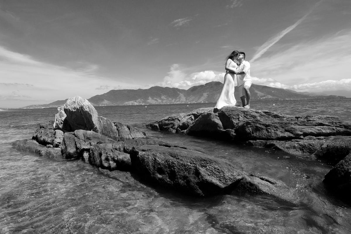 noivos se beijam sobre as rochas