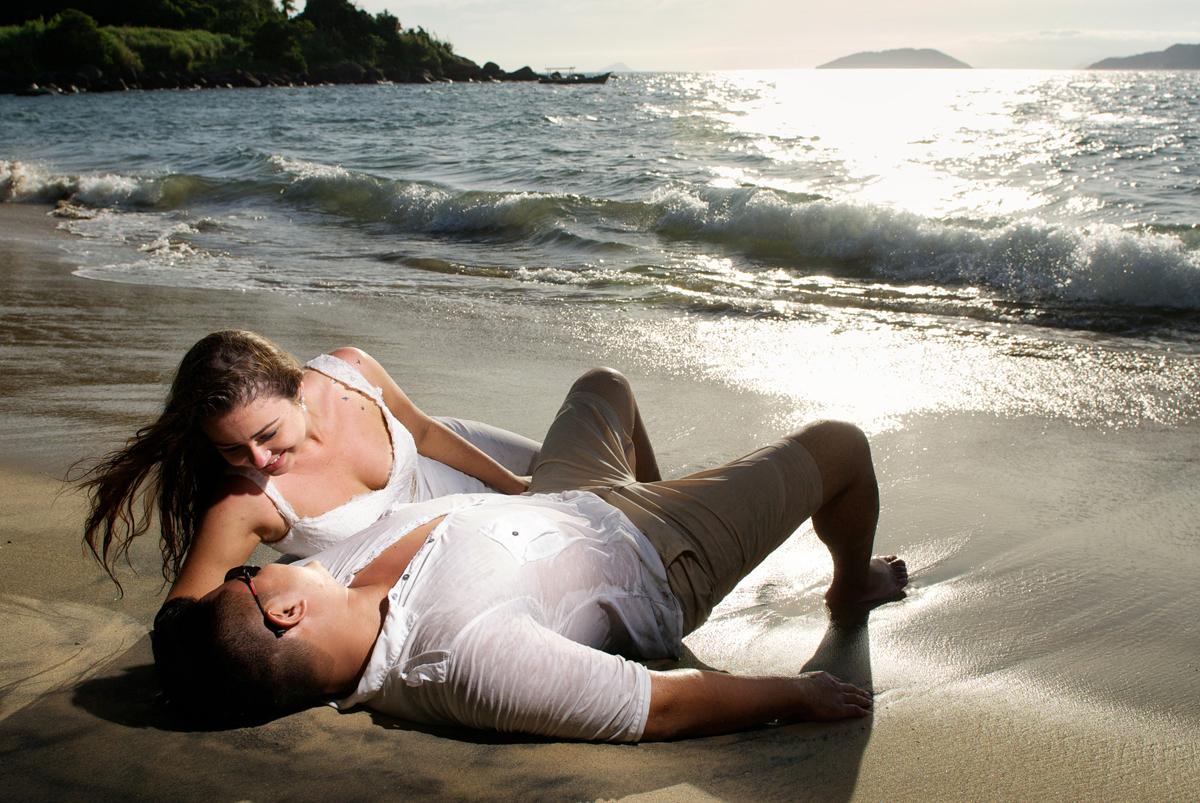 noivos deitam na praia sob o por do sol