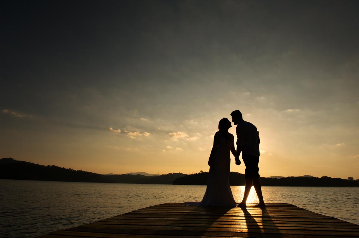 silhueta de noivos na represa