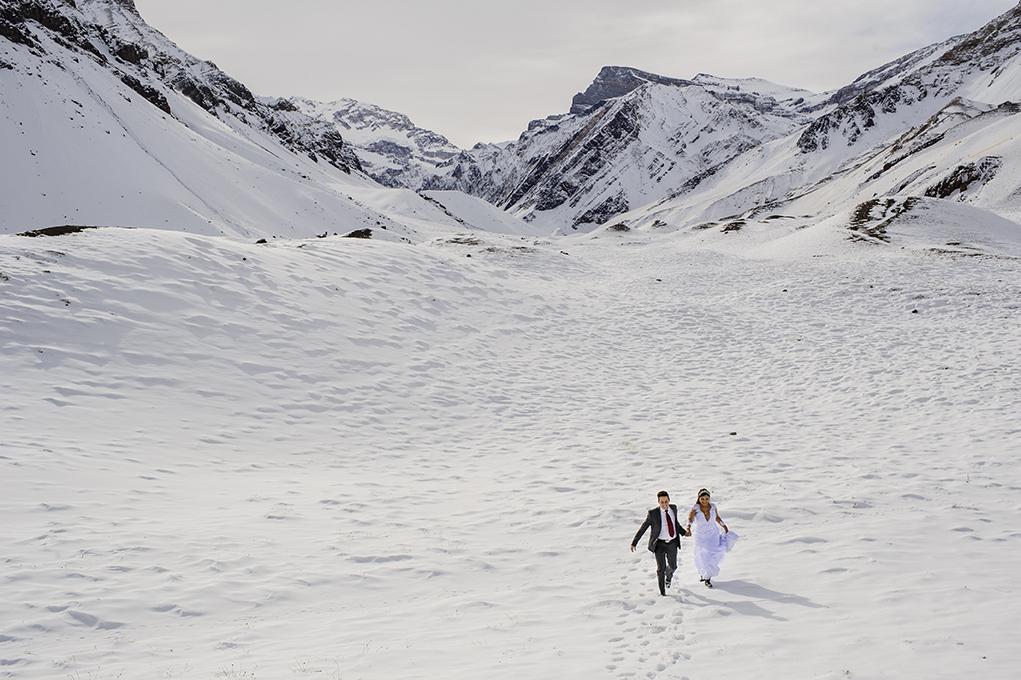 Noivos correndo na neve dos andes