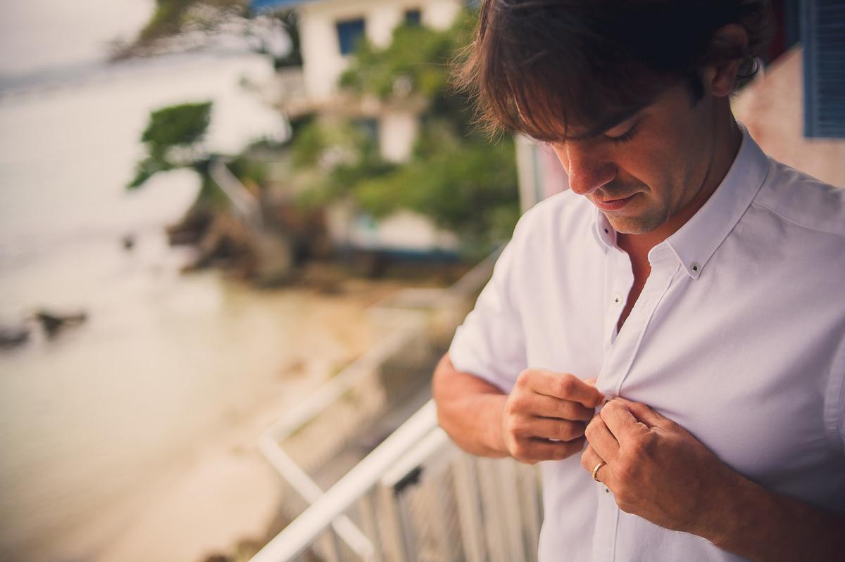 noivo fechando botao da camisa