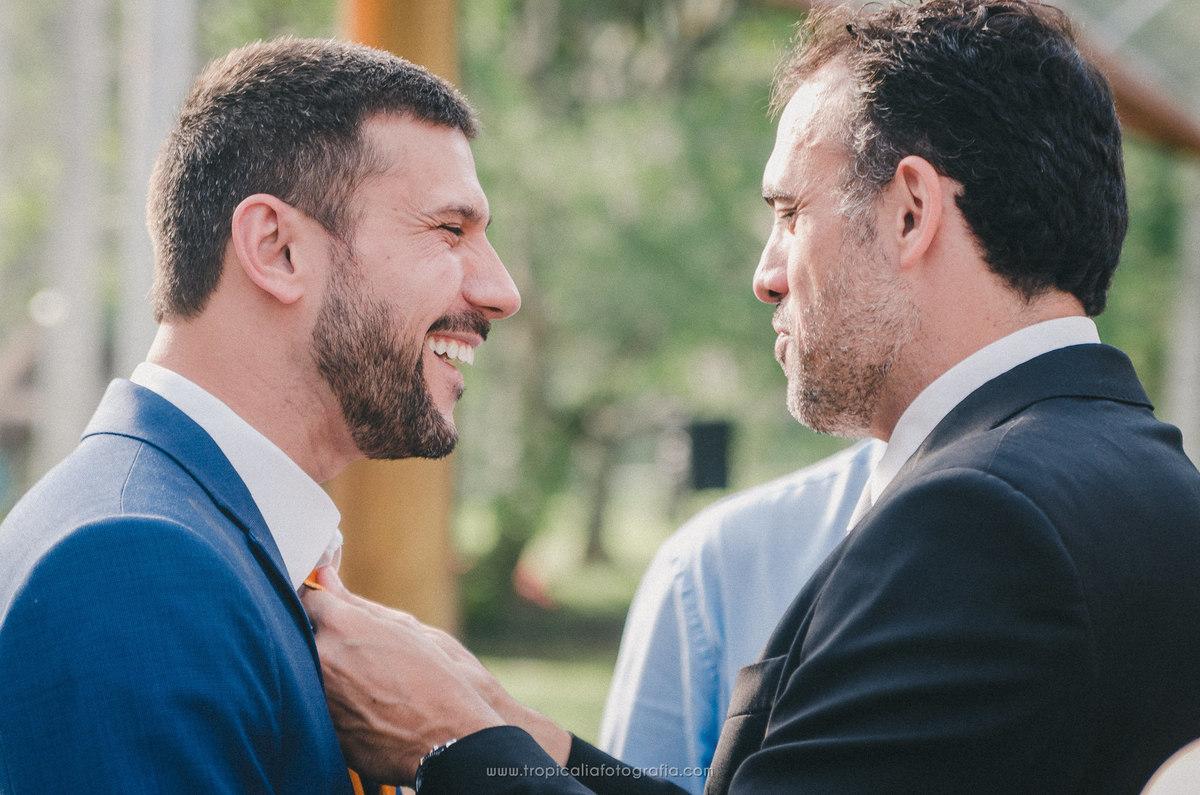 Casamento no Rio de Janeiro. Fotógrafo de casamento em Nova Friburgo. Foto do padrinho ajeitando a gravata do noivo
