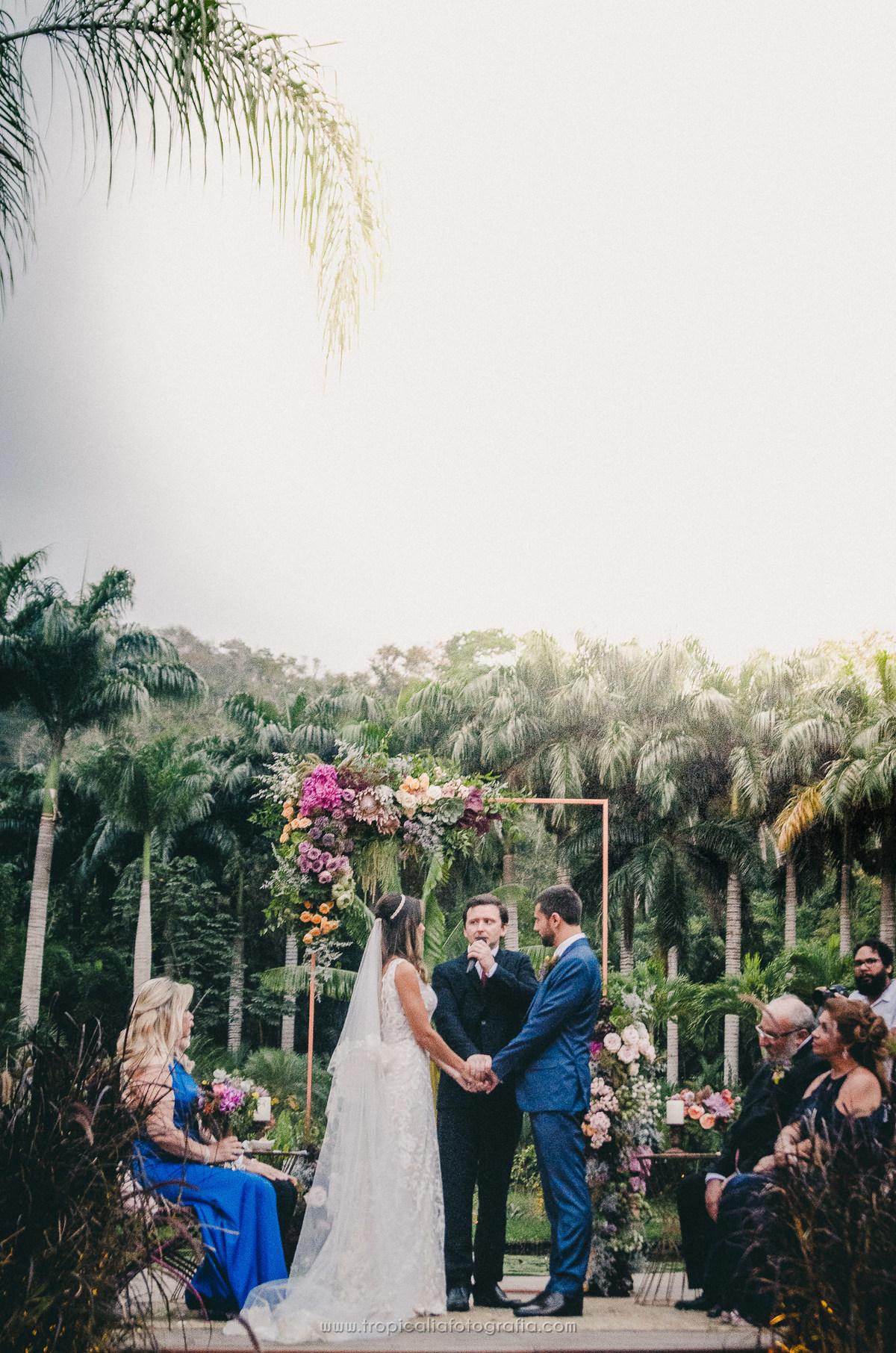 Casamento no Rio de Janeiro. Fotógrafo de casamento em Nova Friburgo. Foto de longe do altar, mostrando os noivos, o celebrante e os pais dos noivos. Ao fundo a decoração do altar com flores e as palmeiras do Lago Buriti.