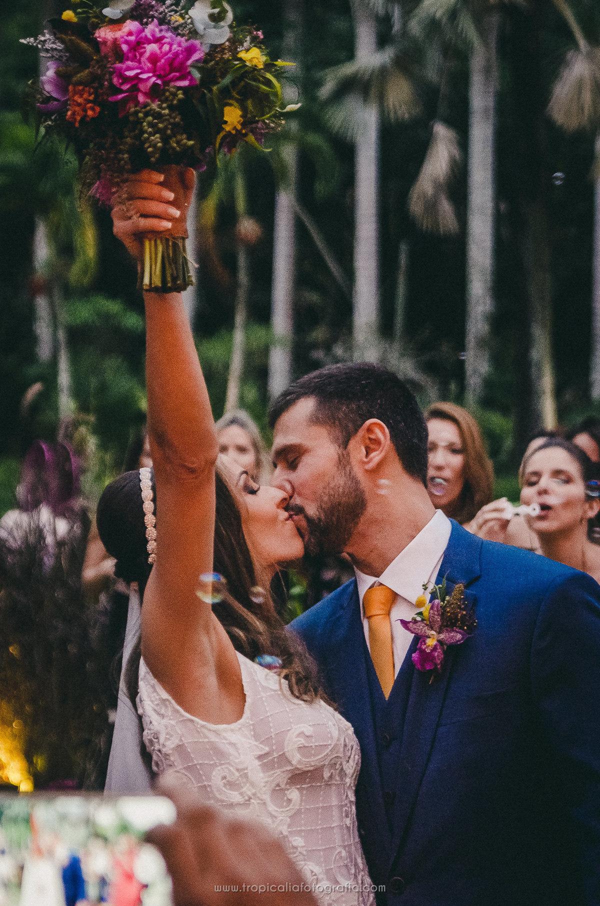 Casamento no Rio de Janeiro. Fotógrafo de casamento em Nova Friburgo. Foto do beijo dos noivos enquanto a noiva levanta o buquê. Foto mostra os convidados ao fundo assoprando bolhas de sabão nesse momento.