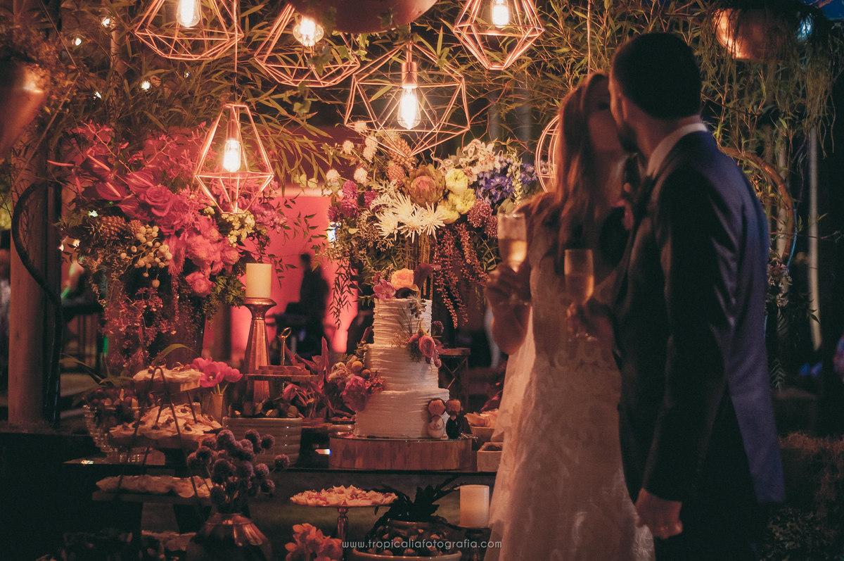 Casamento no Rio de Janeiro. Fotógrafo de casamento em Nova Friburgo. Foto do casal se beijando e ao fundo a mesa do bolo do casamento e decoração com flores e luzes