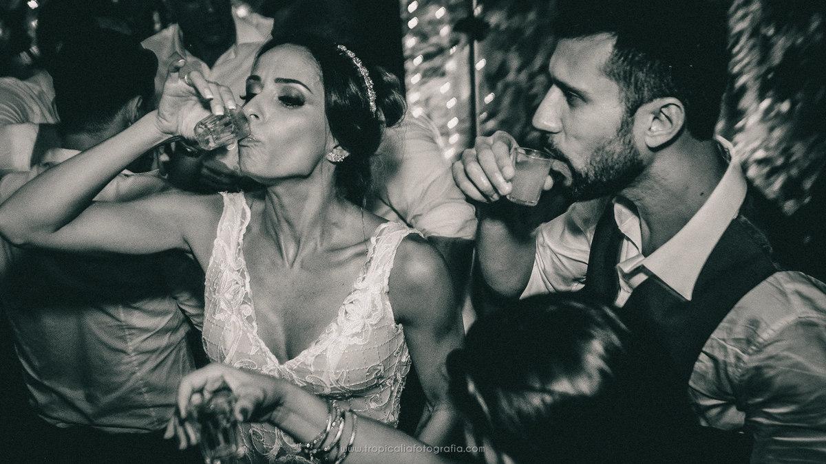 Casamento no Rio de Janeiro. Fotógrafo de casamento em Nova Friburgo. Foto em preto e branco dos noivos bebendo um shot de tequila durante a festa de casamento