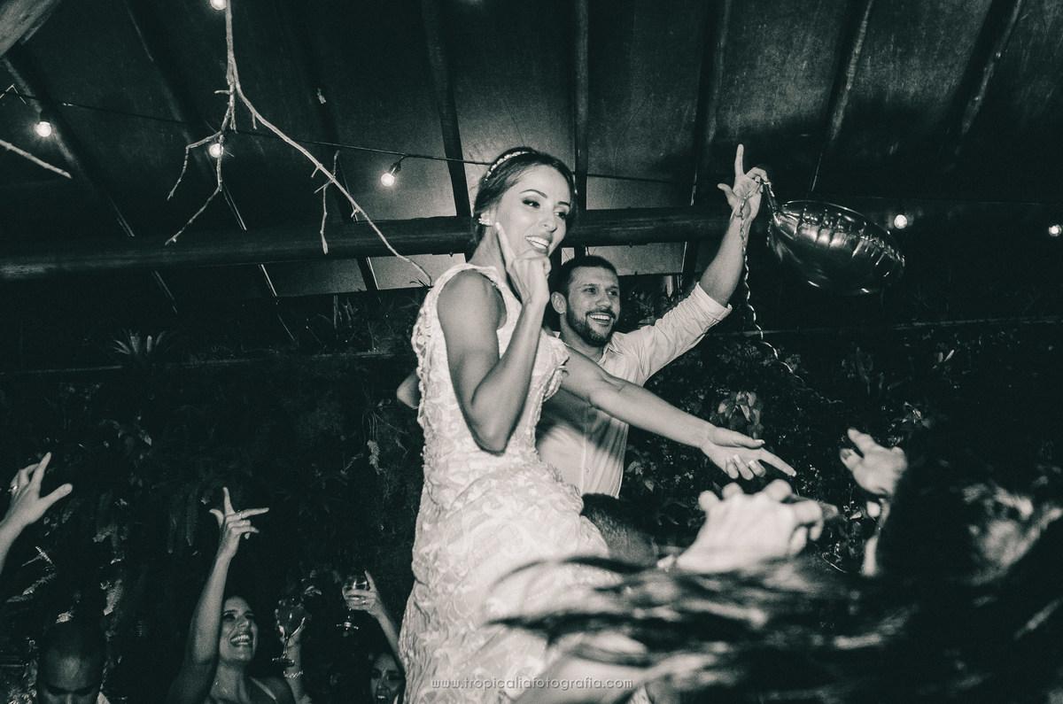 Casamento no Rio de Janeiro. Fotógrafo de casamento em Nova Friburgo. Foto em preto e branco dos noivos sendo levantados na festa de casamento pelos convidados