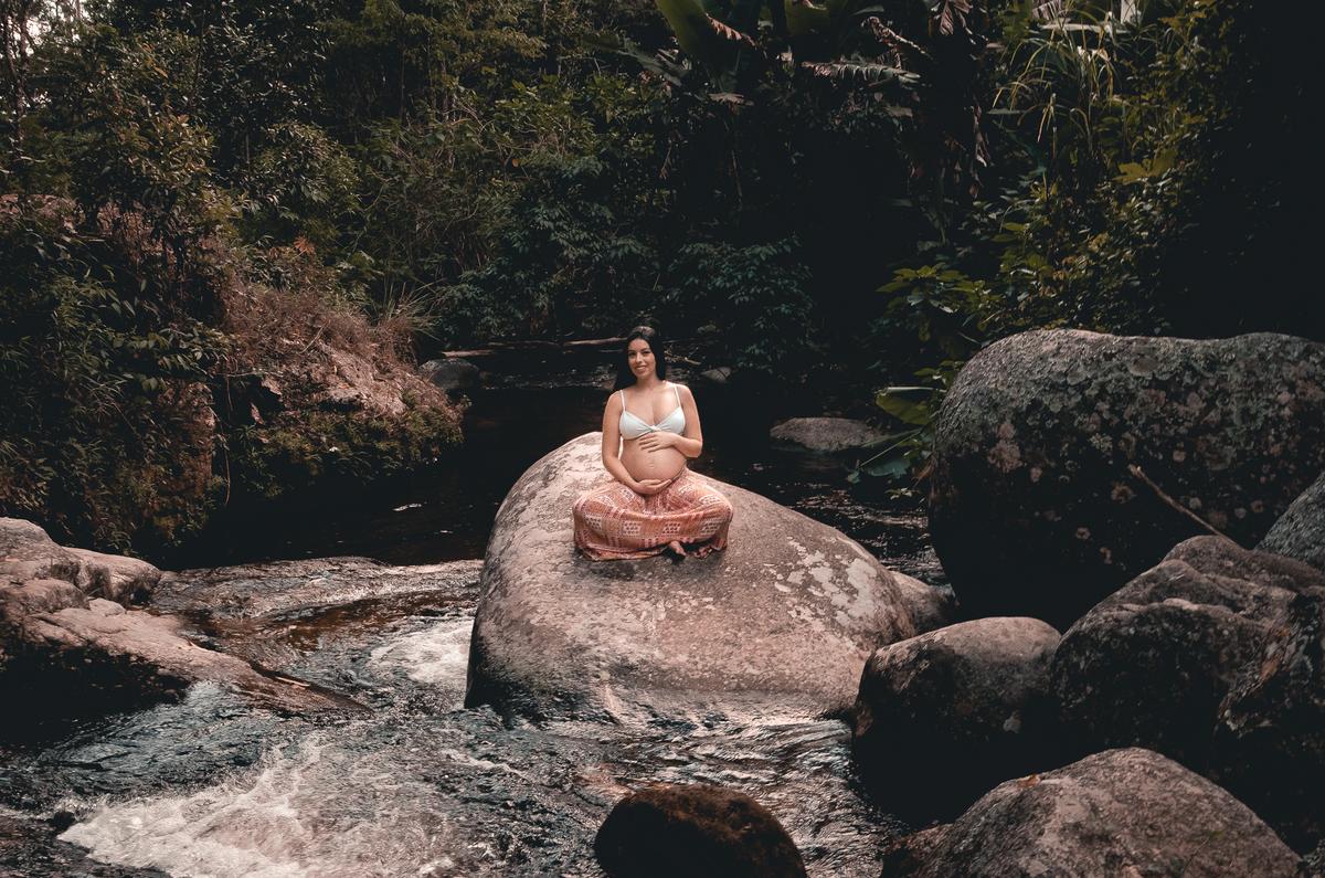 Ensaio de Gestante em Nova Friburgo,  foto minimalista da gestante sentada em uma pedra no meia de uma queda d'água