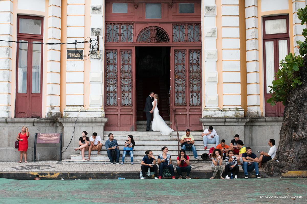 noivos abraçados na porta com pessoas sentadas