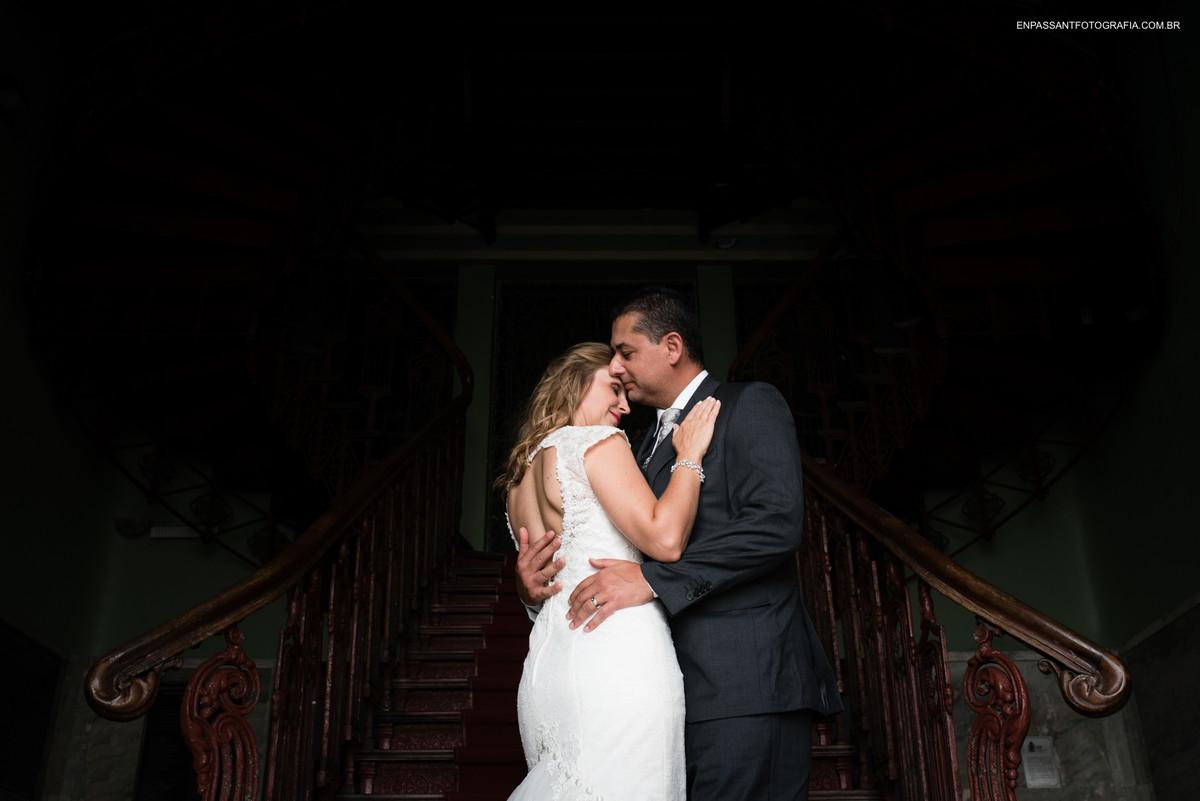 noivos abraçados em frente a escada