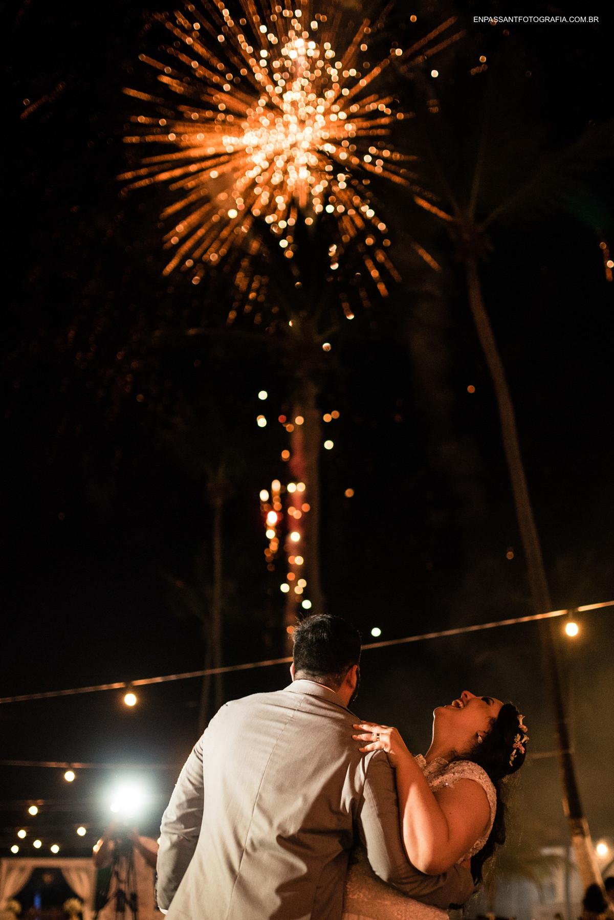 noivos se abraçam com fogos de fundo