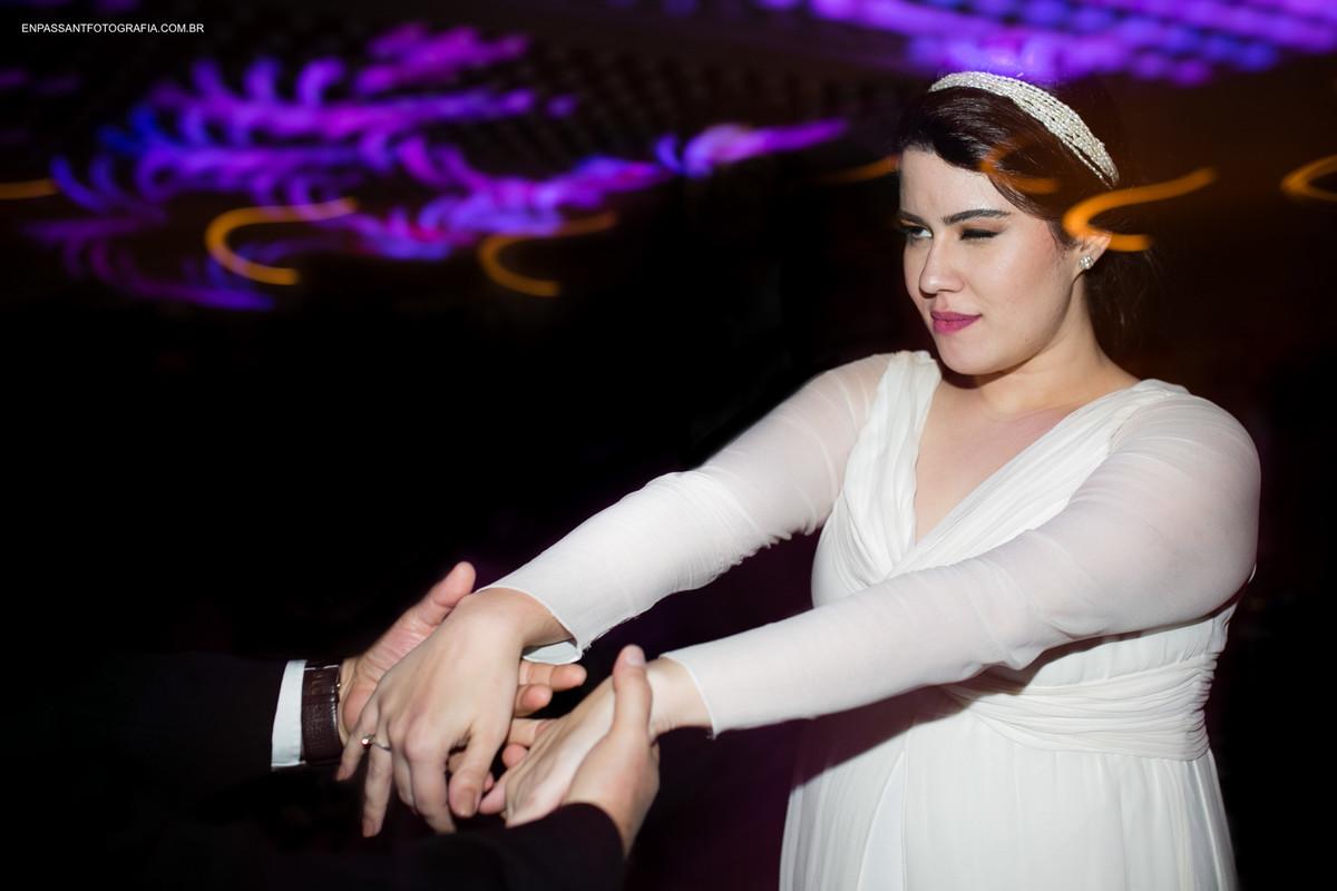 noiva e noivo de mãos dadas e ela piscando o olho