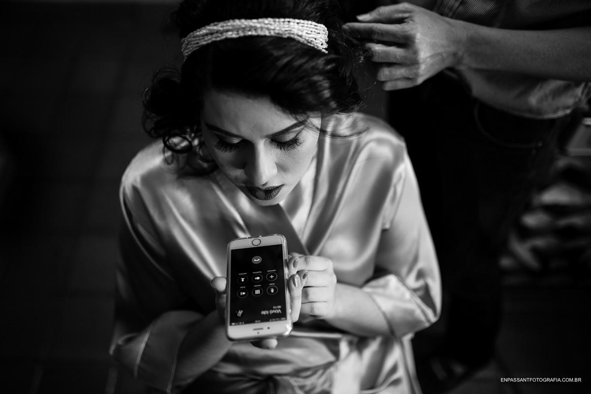 noiva conversando ao celular enquanto maquiador arruma seu cabelo