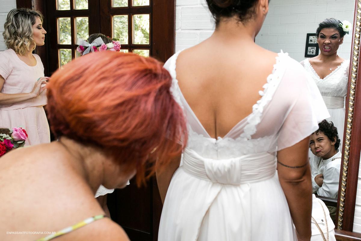 mãe da noiva ajuda a fechar o vestido