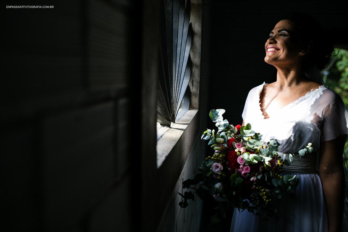 noiva sorrindo em frente a janela