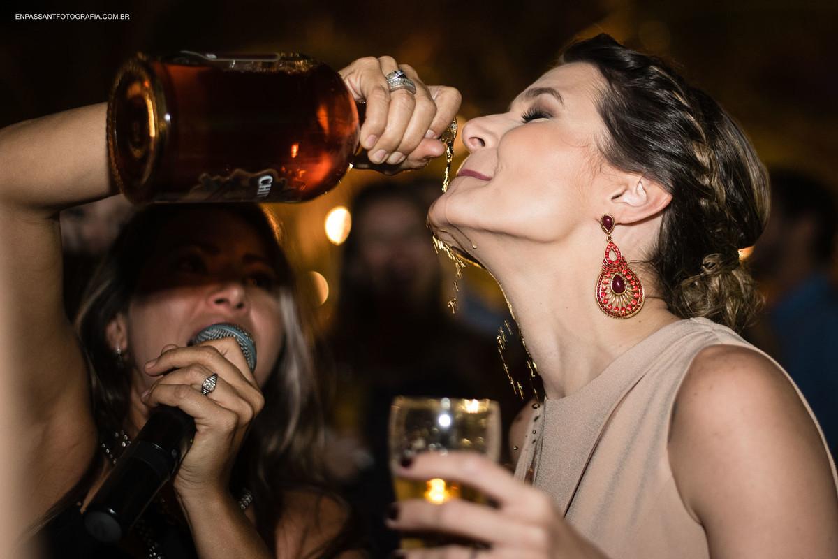 mulher derrama bebida na boca de outra