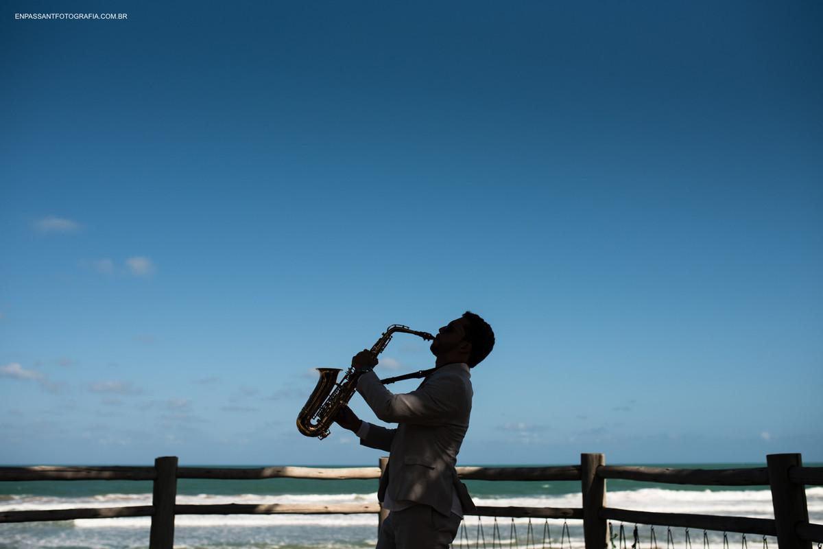 noivo tocando sax na praia