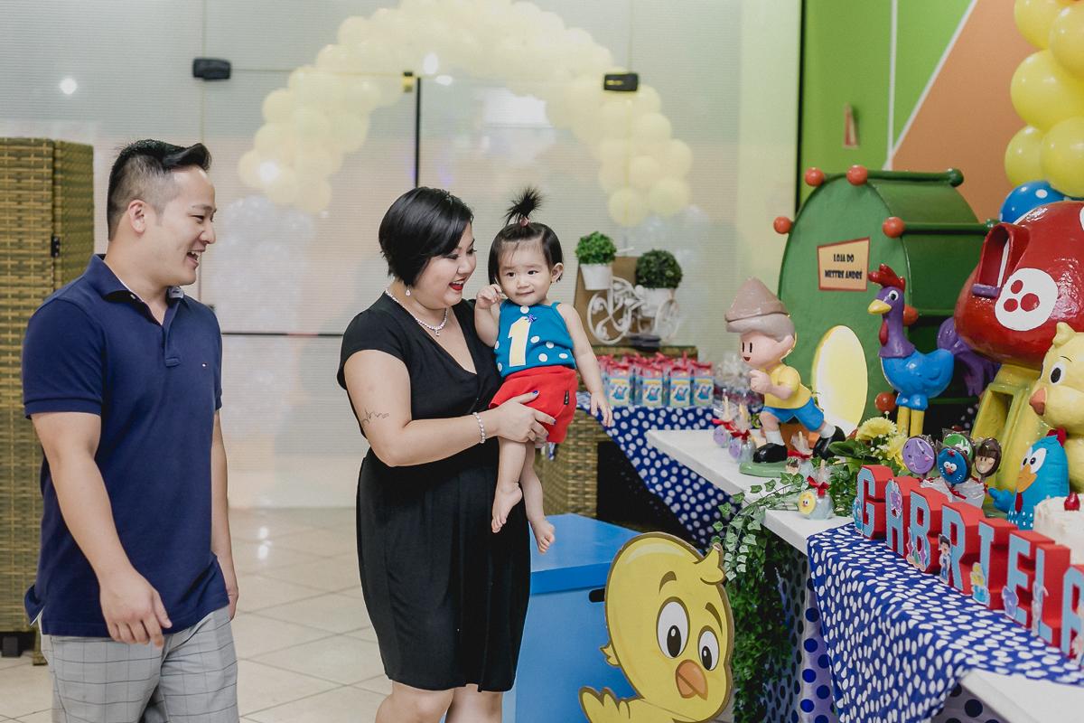 familia entrando na festa de 1 ano da Gabi e olhando a mesa do bolo