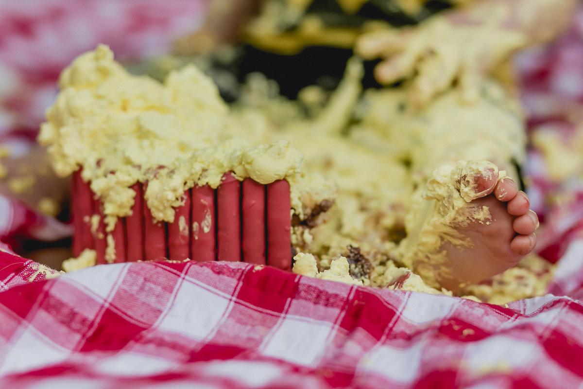 detalhes da sola do pe do joao misturada com o bolo no final do ensaio smash the cake