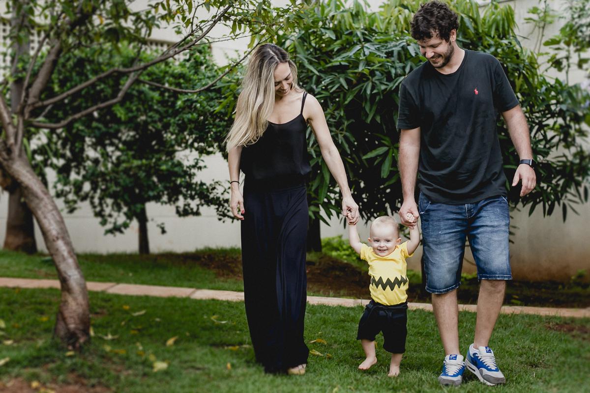 Joao caminhando com o papai e a mamae no ensaio familia