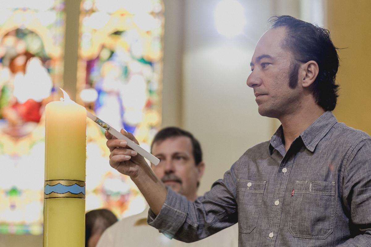 padrinho acendendo a vela do batizado