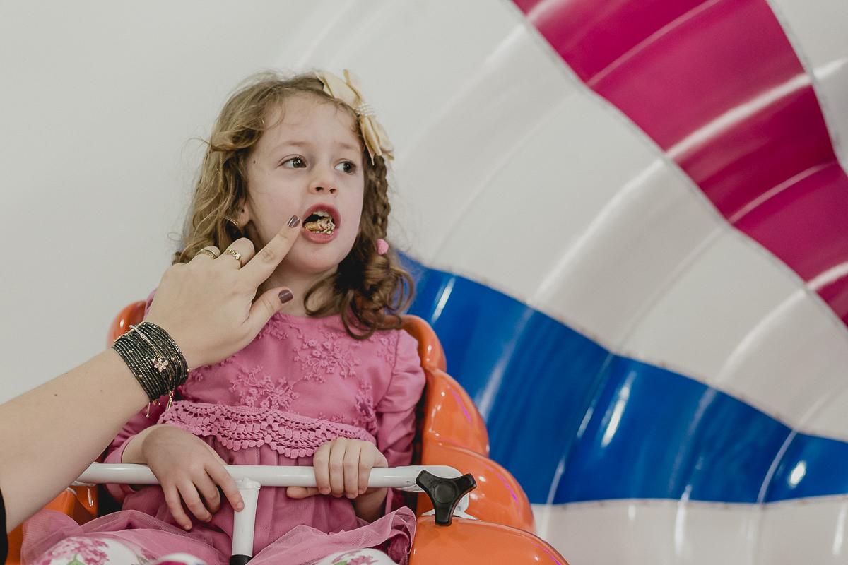 sofia comendo salgadinho enquanto brinca na roda gigante