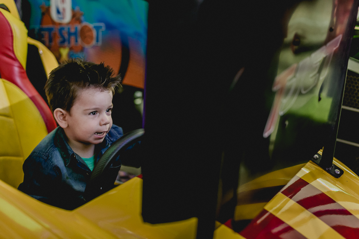 Lucas brincando de corrida no jogo de carro no Espaço Diversão e Arte - Zona Norte - SP