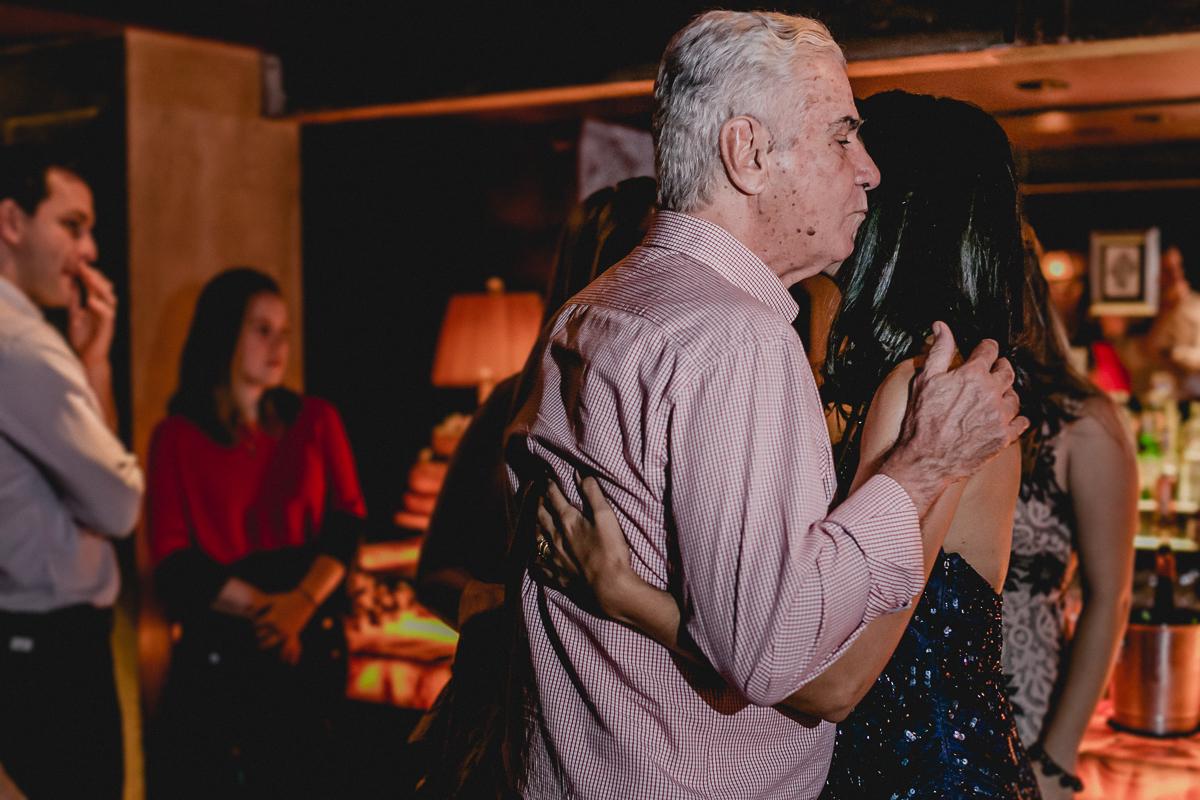 Clarissa recebendo um abraço e beijo do seu pai no começo da festa