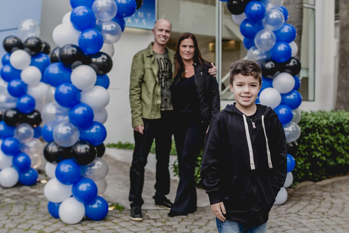 felipe e os pais posando para a foto na frente do buffet funny days