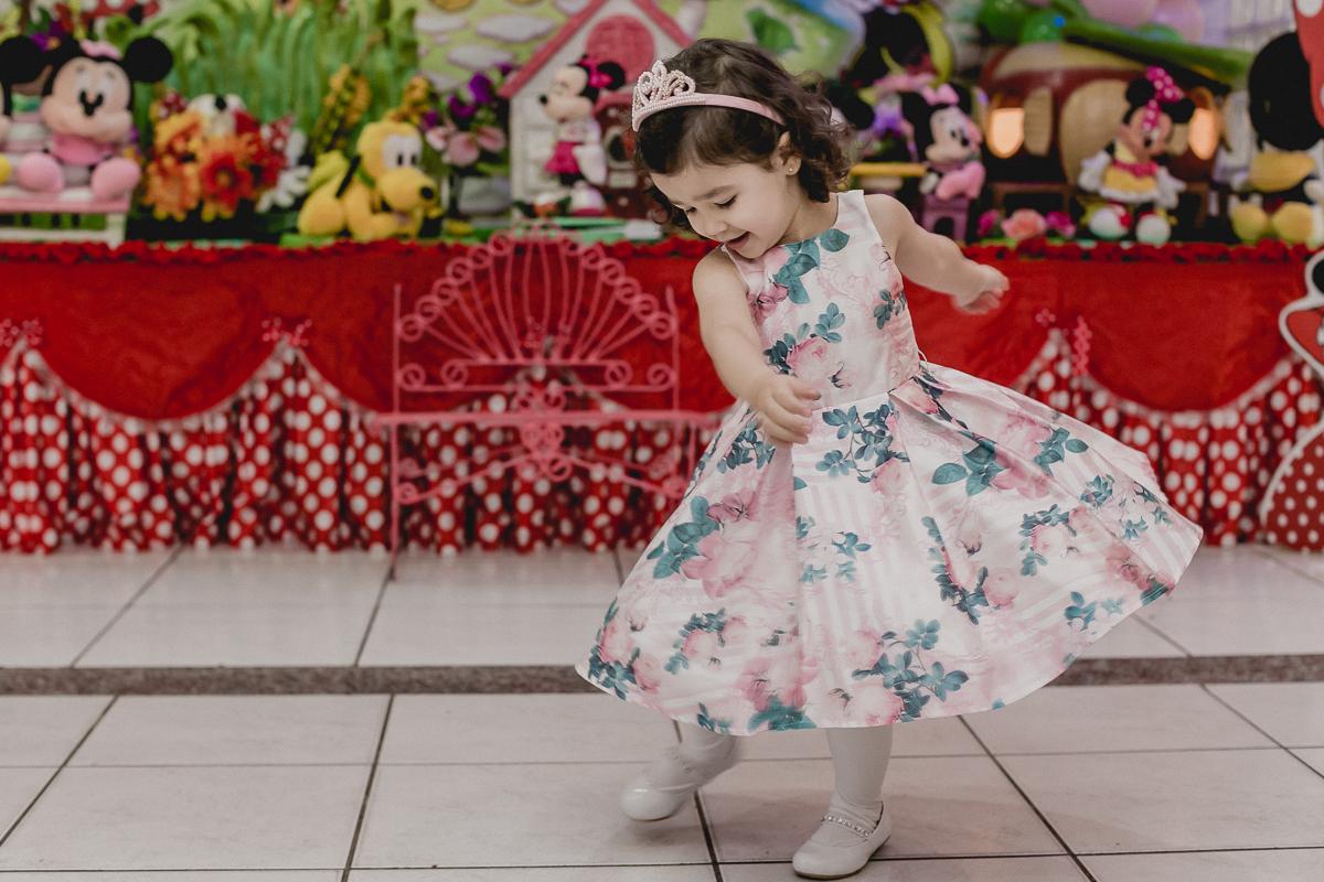 dançando e balançando o vestido na frente da mesa do bolo