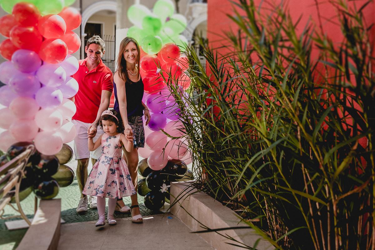 Alice chegando de mãos dadas com os pais para a festa de 3 anos