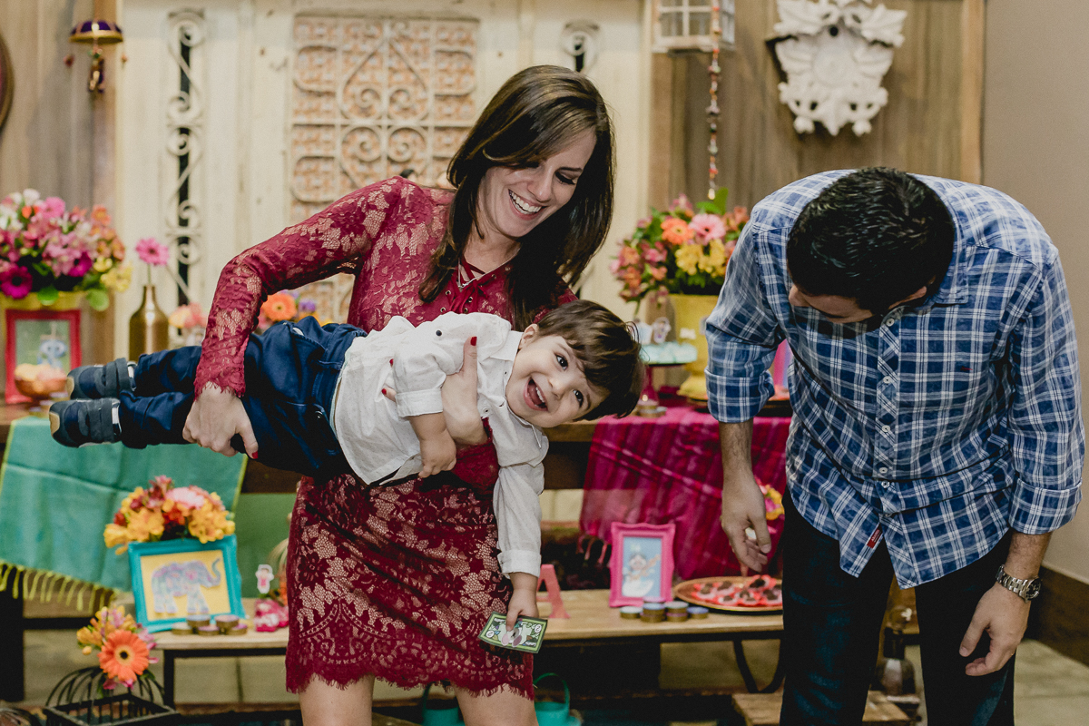 brincando com os pais na frente da mesa do bolo