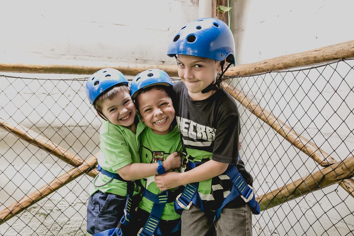 crianças de capacete e dando risada prontas para ir na tirolesa