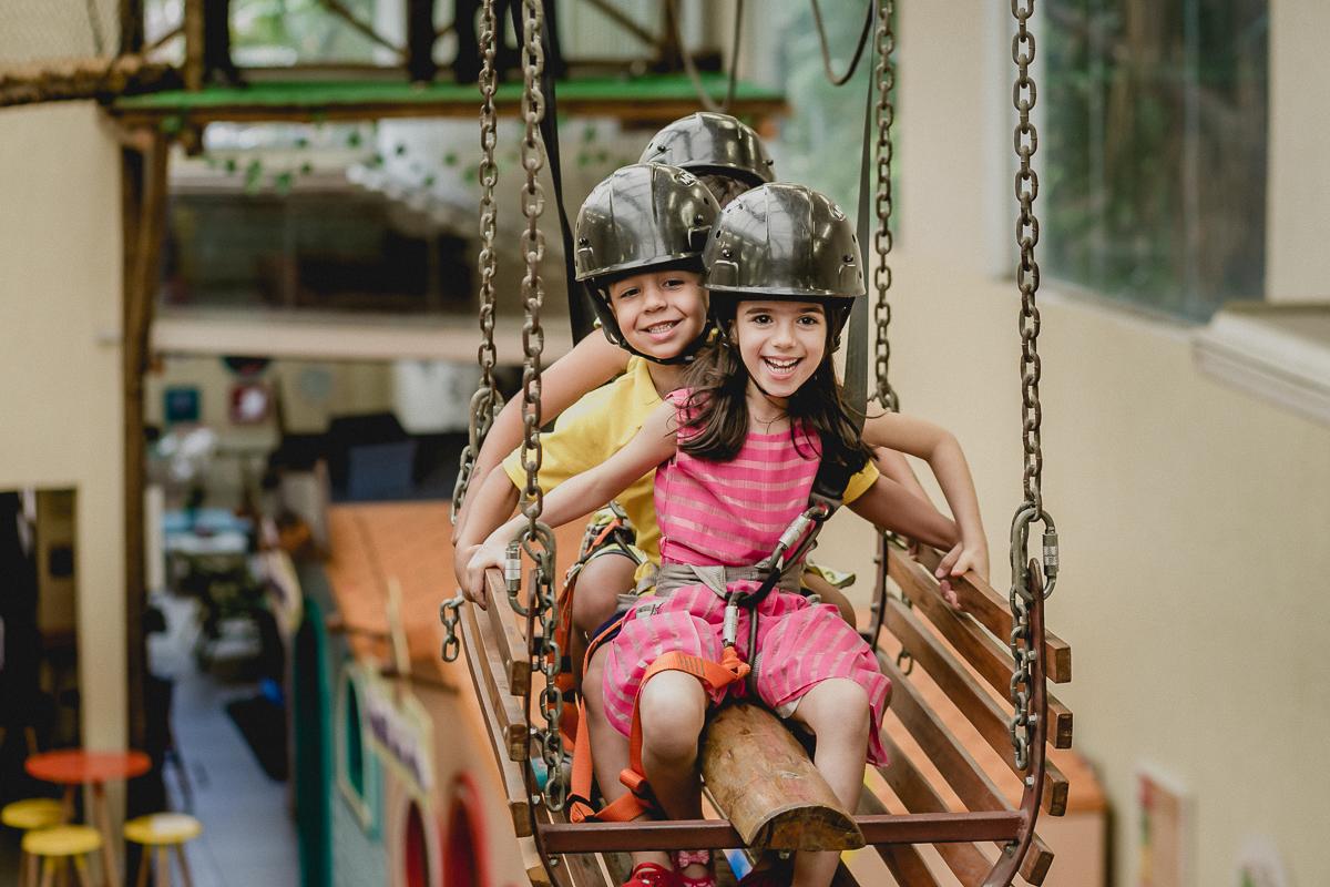 crianças atravessando a tirolesa no carrinho