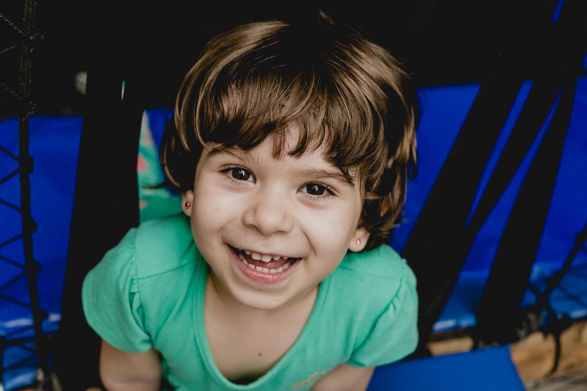 menina simpatica sorrindo para a foto