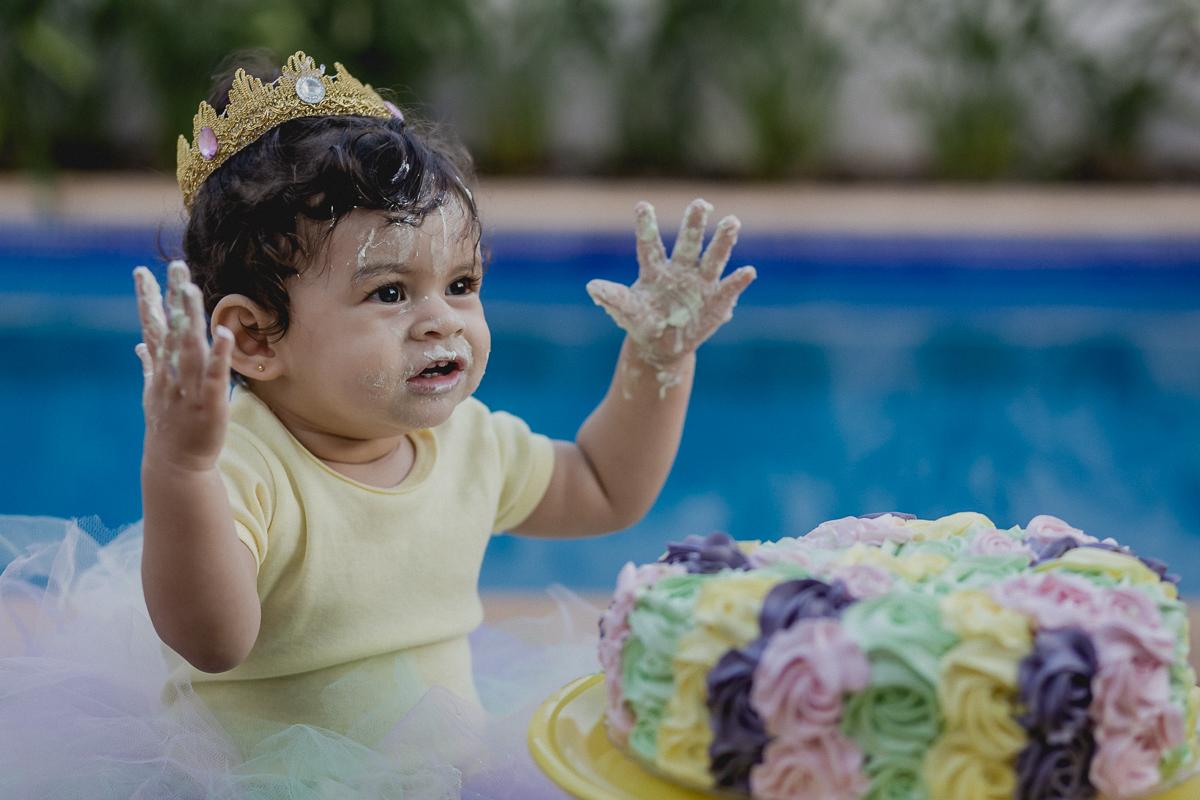 lia abrindo os bracinhos e feliz brincando com o bolo