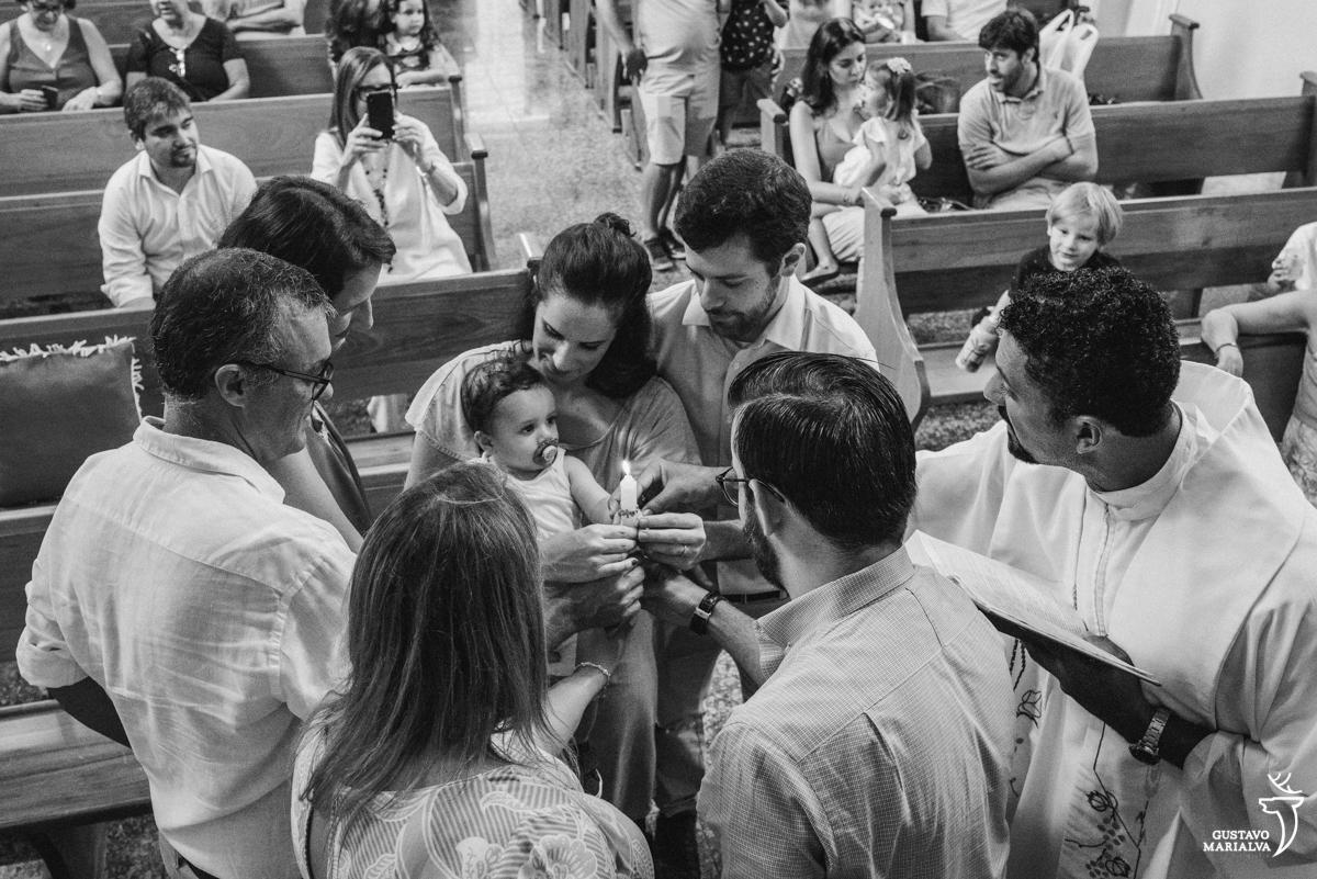 f25a748c38a padre abençoa bebe que é observado pelos pais e convidados