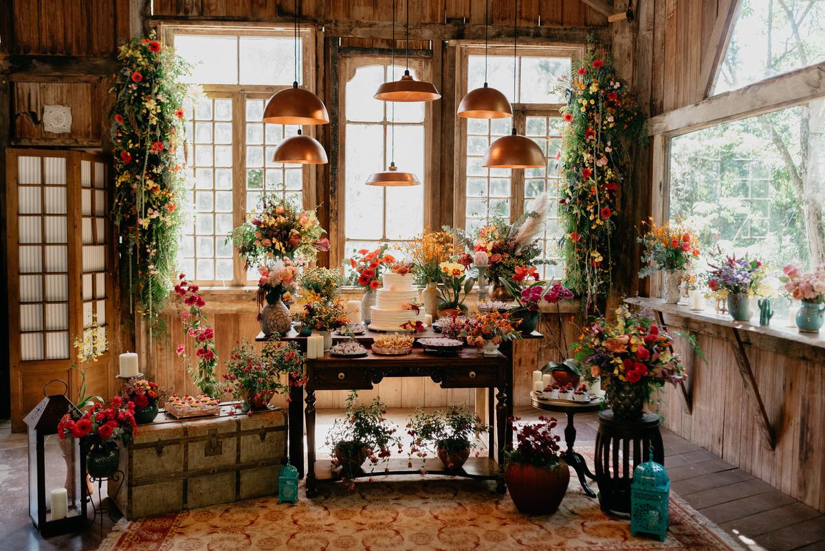 mesa de casamento com estilo industrial, com flores coloridas no celeiro.