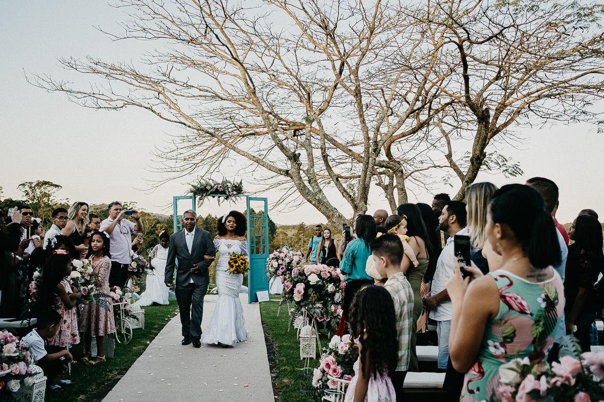 entrada da noiva cerimonia no campo casamento de dia fotografia de casamento noiva com o pai vestido de noiva buque de girassol fotos por caio henrique fotografo de casamento sao paulo zona leste