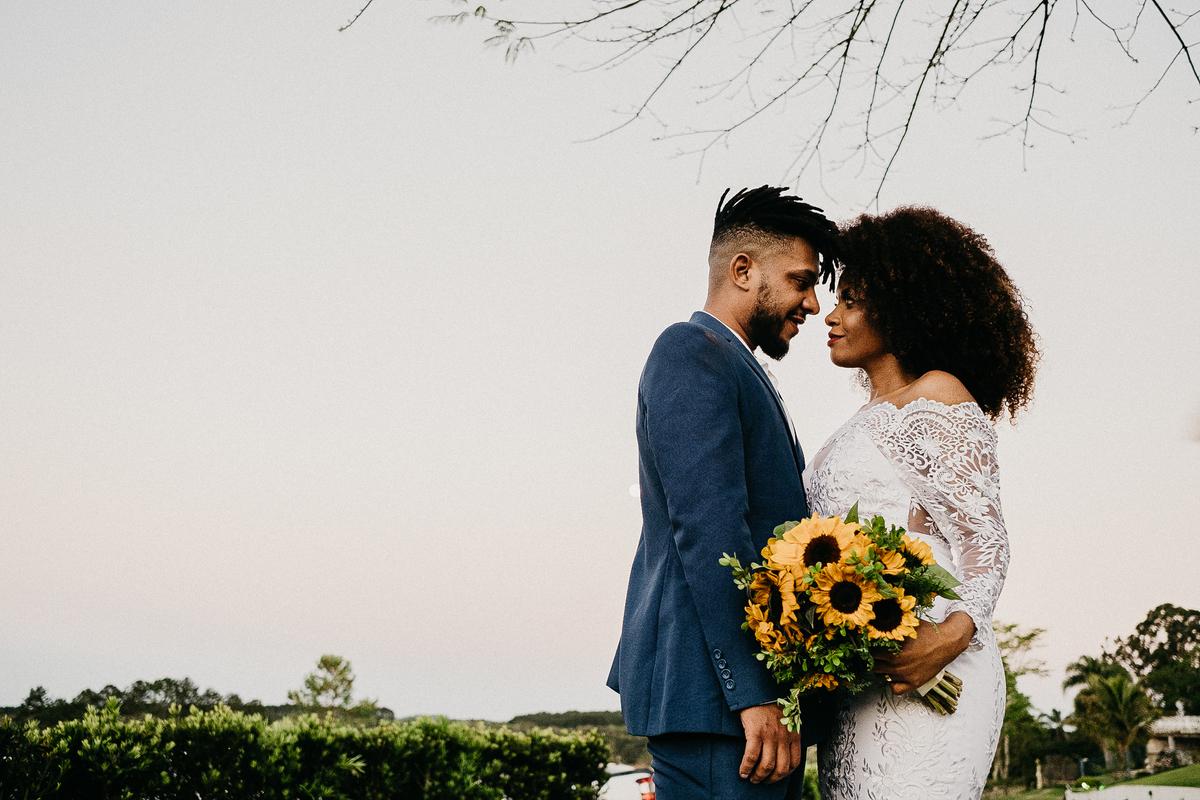 noivos sorrindo saida dos noivos cerimonia ao por do sol fotografia de casamento de dia fotografos de casamento em sao paulo noivos afros  trash th dress buque de girassol