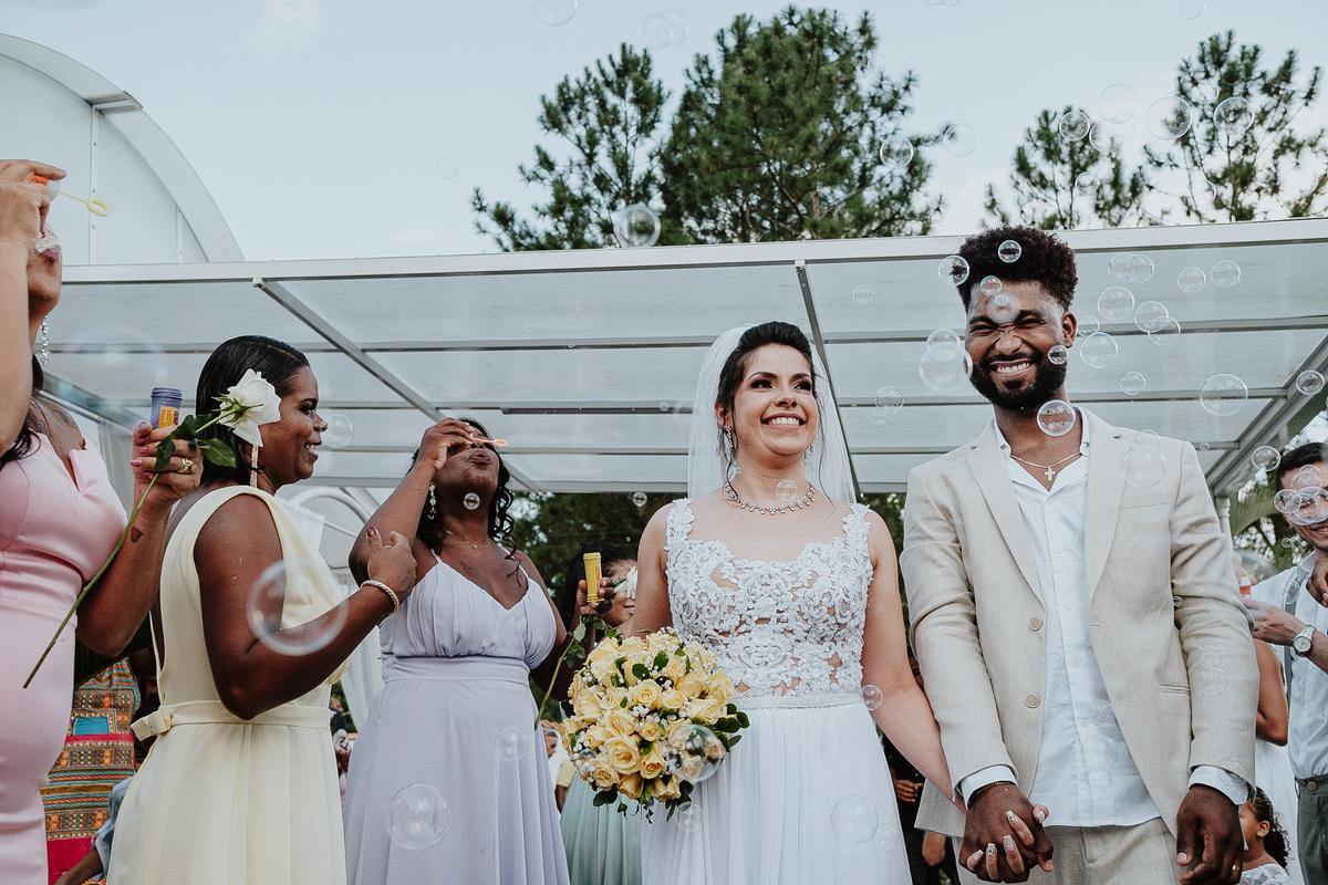 saida do casal cerimonia no campo fotografia de casamento por caio henrique rancho ribeiros casal sorrindo com bolinhas de sabao