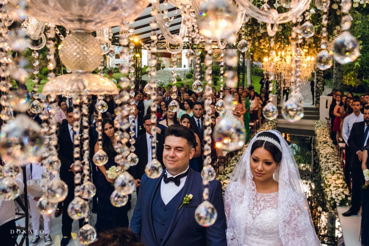 44ac50c6854a Noiva e noivo na cerimonia com lustre da decoração da concept party.