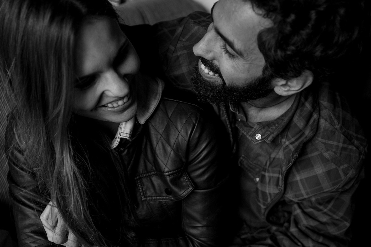 foto bem divertida do casal se olhando e rindo espontaneamente, com uma luz lateral linda vindo de uma porta, para deixar a foto mais linda ela foi feita em branco e preto.