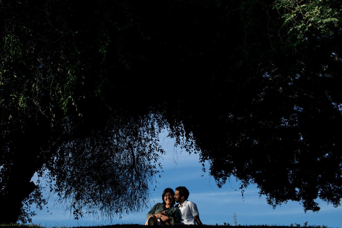 foto do casal sentados entre uma molduras de arvores, ao fundo um lindo céu azul.