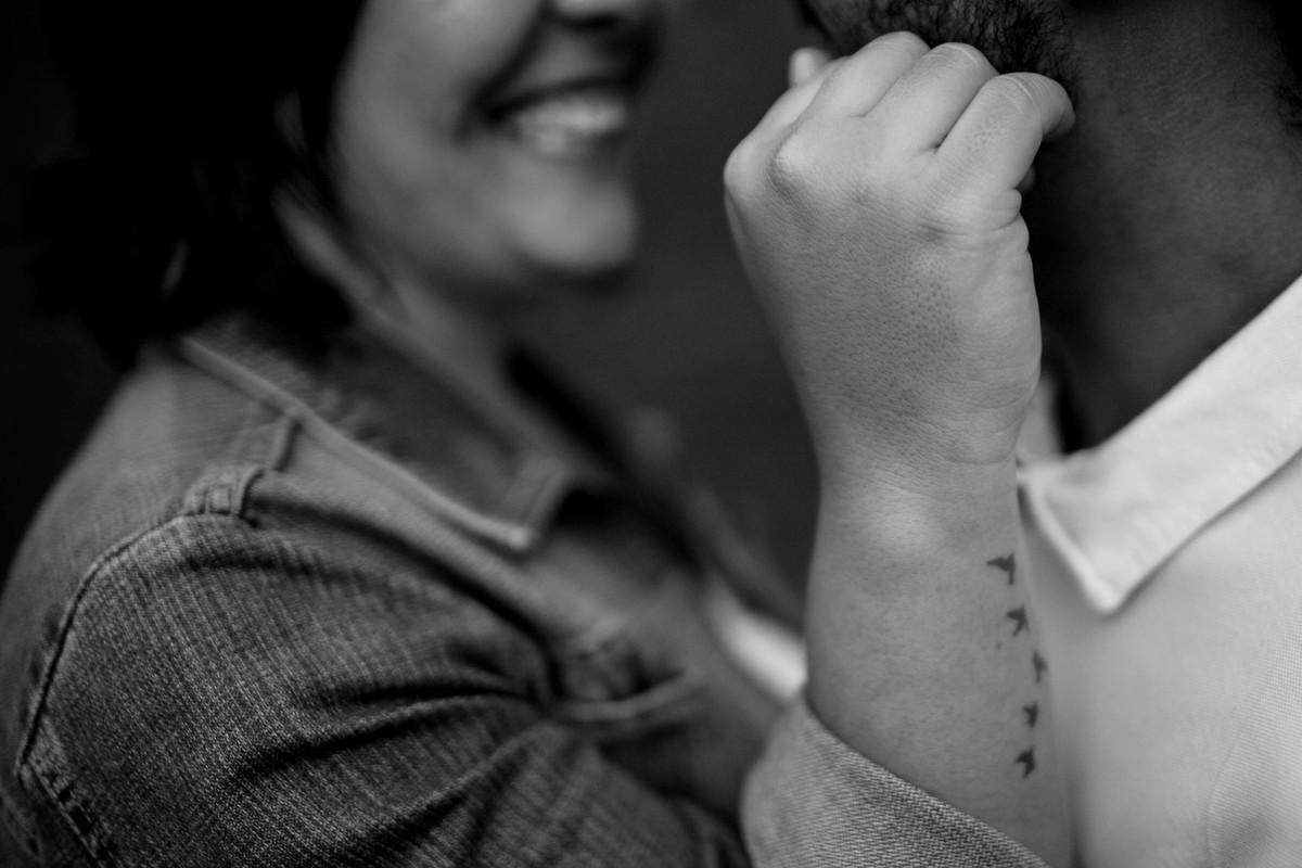 foto do detalhe da tatuagem do braço da noiva, com o lindo sorriso do casal ao fundo em desfoque.