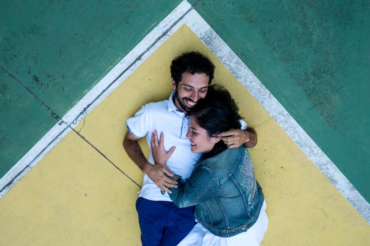 foto do casal deitado no cha da quadra de basquete, o angulo que utilizei, faz parecer que eles estão dentro do triangulo amarelo da bandeira do brasil, com o contorno verde, foto muito criativa.